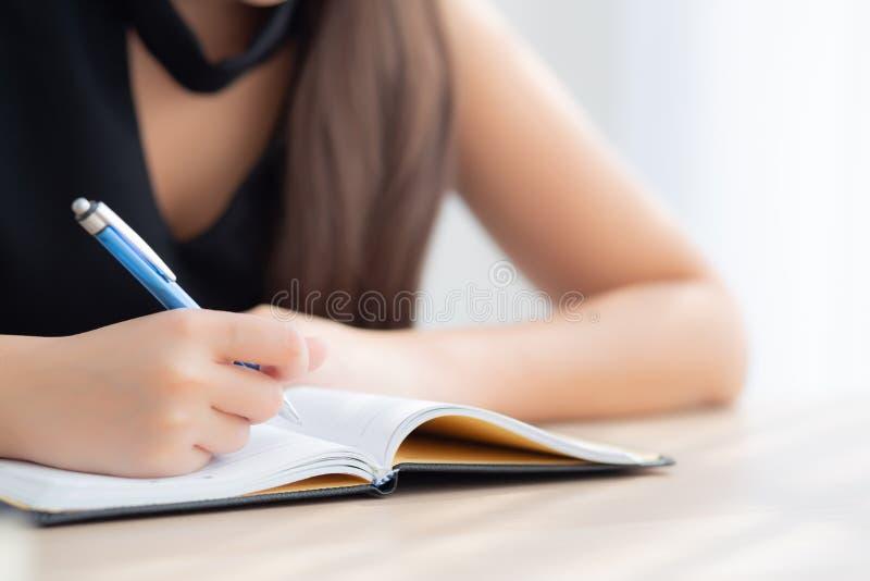 Estudo de assento da mulher asiática da mão do close up e aprendizagem escrevendo o caderno e o diário na tabela na sala de visit fotos de stock