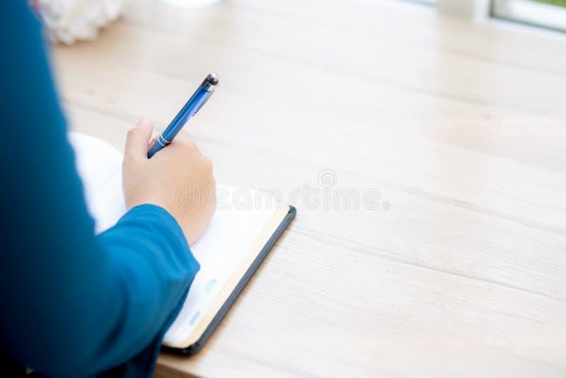 Estudo de assento da mulher do asiático da mão do close up e aprendizagem escrevendo o caderno e o diário na tabela dentro na loj imagens de stock royalty free