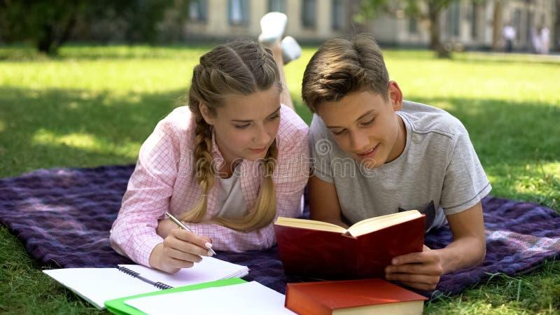 Estudo dos estudantes, encontro na manta no parque, leitura e fatura de anota fotos de stock royalty free
