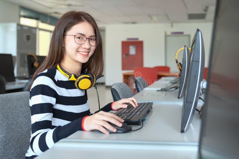 Estudo novo do estudante fêmea na biblioteca escolar, ela que usa o portátil e que aprende em linha, de volta à faculdade do conh imagem de stock