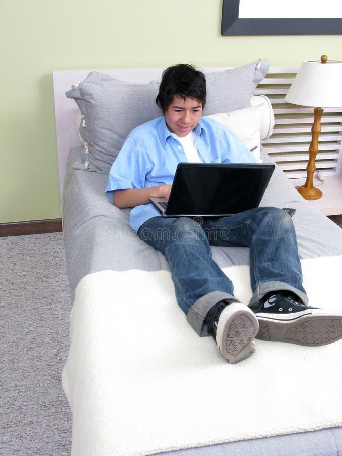 Estudo novo na cama com portátil foto de stock