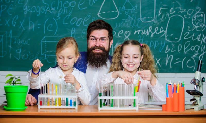 Estudos da pesquisa Professor de ci?ncias e alunos que fazem o trabalho de pesquisa Crianças do professor e de escola primária qu fotos de stock royalty free