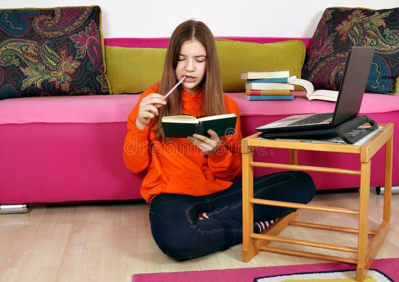 Estudos do adolescente com um port?til e um livro fotografia de stock royalty free