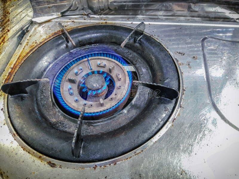 Estufa de gas vieja de la encimera de Rusty Propane con las llamas azules fotos de archivo