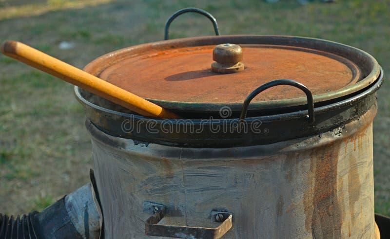 Estufa hecha fuera de barril y del pote cubierto grande con la cuchara de madera que enarbola de ella fotografía de archivo libre de regalías