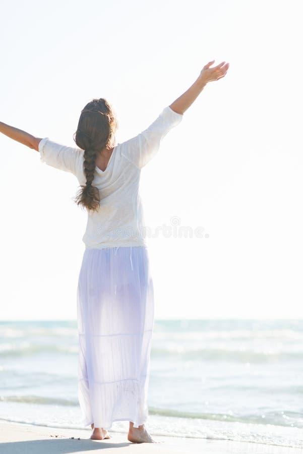 Esultanza della giovane donna sulla costa di mare. retrovisione fotografia stock