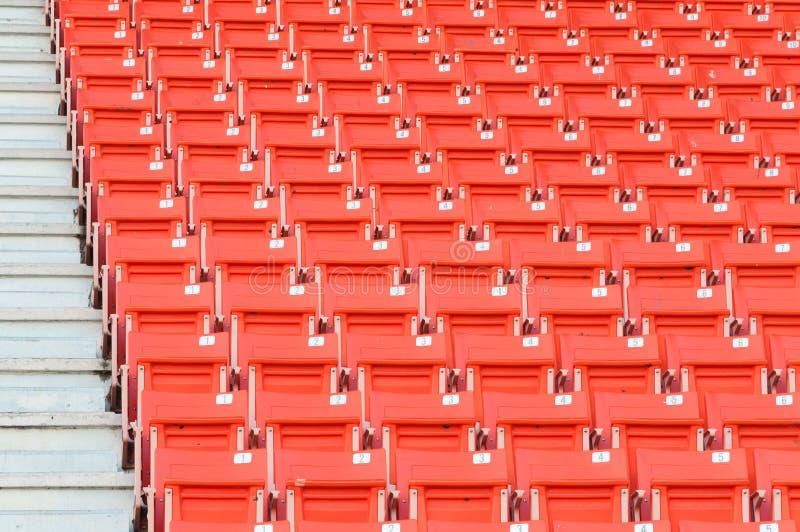Esvazie assentos alaranjados no estádio, passagem das fileiras do assento em um estádio de futebol foto de stock