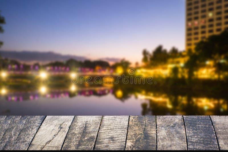 Esvazie do formulário da mesa e da luz de madeira do bokeh do scape da cidade da noite imagem de stock royalty free