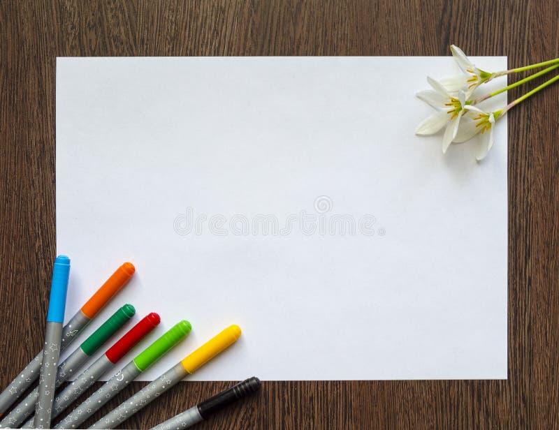 Esvazie a folha de papel branca para o texto em um fundo de madeira escuro Em torno dele são as canetas com ponta de feltro e as  fotos de stock royalty free