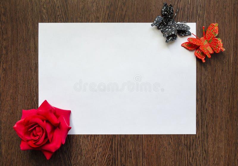 Esvazie a folha de papel branca para seu texto em um fundo de madeira escuro da tabela Há flores coloridos e borboletas em torno  fotografia de stock