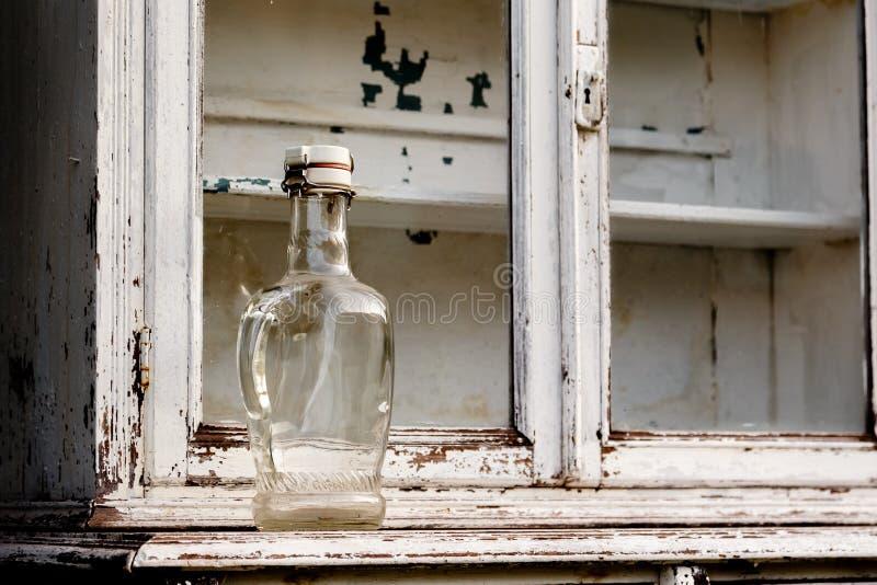 Esvazie a garrafa de vidro em um armário de cozinha velho foto de stock royalty free