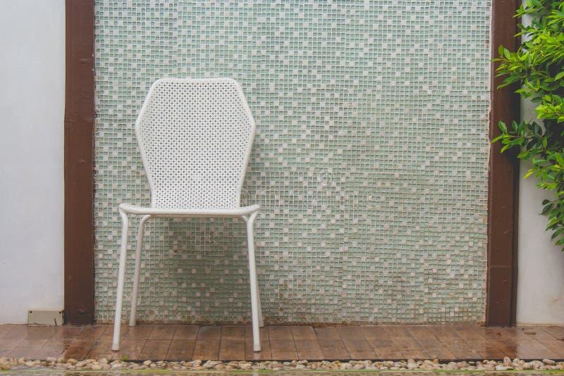 Esvazie o ajuste plástico branco da cadeira no assoalho de madeira com fundo da parede do mosaico fotografia de stock royalty free