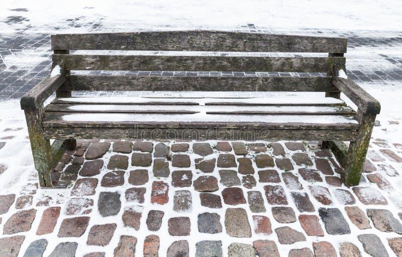 Esvazie o banco de madeira coberto com a neve no inverno foto de stock royalty free