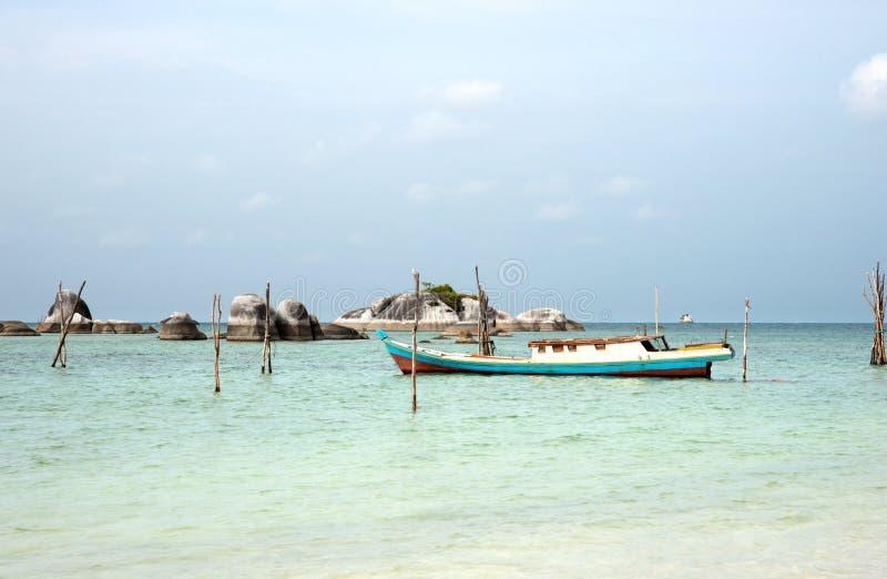 Esvazie o barco de pesca entrado na costa colorida turquesa do oceano perto da praia branca da areia e com as rochas no horizonte imagem de stock royalty free