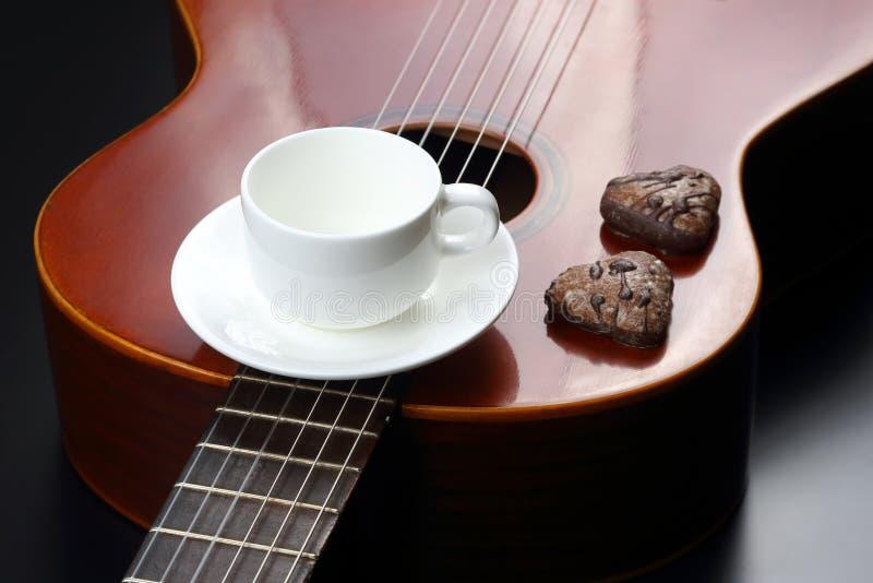 Esvazie o copo e as cookies de café branco na guitarra acústica imagem de stock