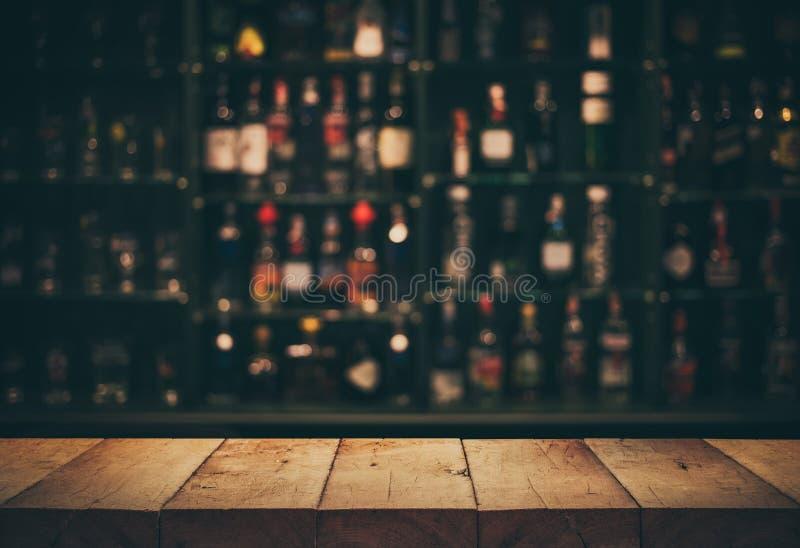 Esvazie a parte superior da tabela de madeira com a barra e as garrafas contrárias borradas imagens de stock