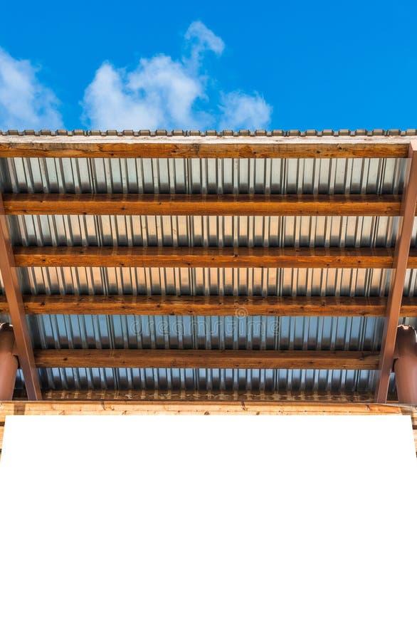 Esvazie a placa de conta branca do espaço com o telhado da madeira e do zinco com s azul fotografia de stock royalty free