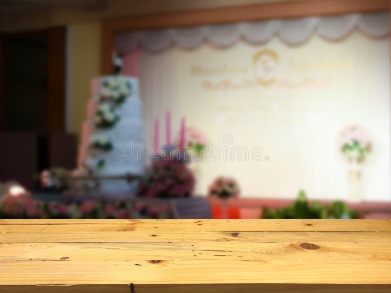 Esvazie a plataforma de espaço de madeira da tabela e o backg borrado do salão do casamento imagem de stock royalty free