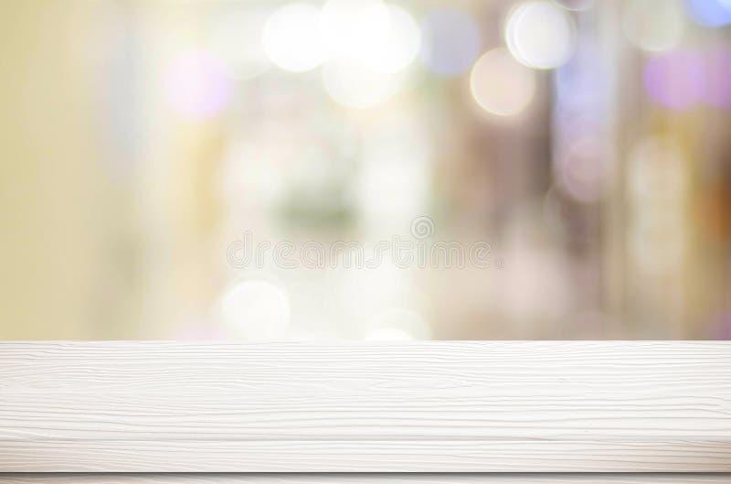 Esvazie a tabela branca e o fundo borrado do bokeh da loja, di do produto