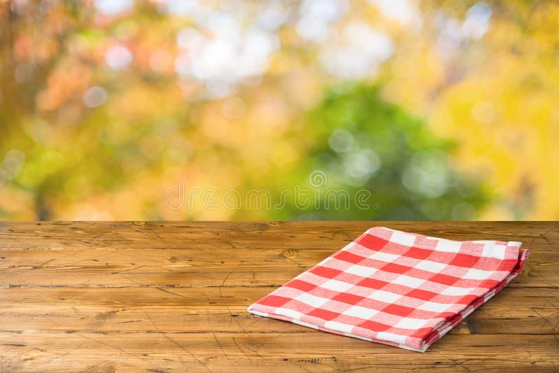 Esvazie a tabela de madeira com toalha de mesa sobre o fundo do parque natural do outono imagem de stock royalty free