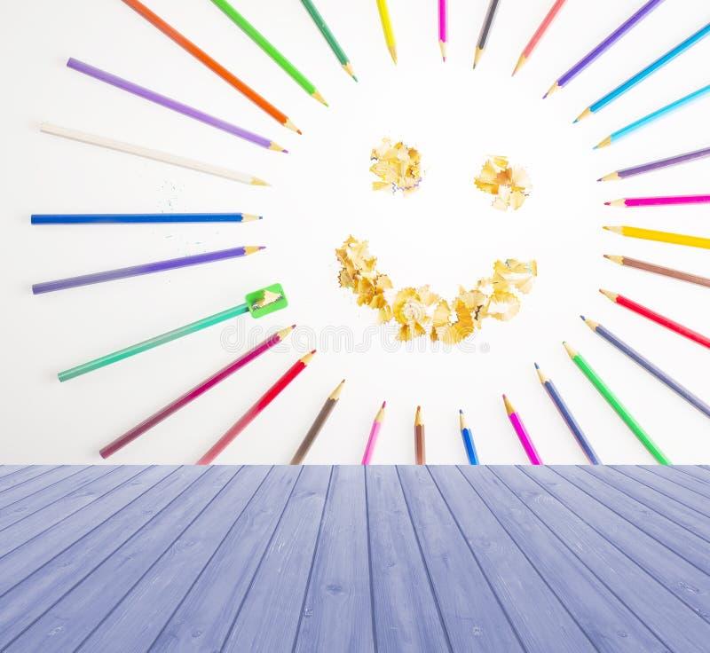 Esvazie a tabela de madeira da plataforma com o sol de sorriso arranjado dos pastéis e do lápis que apontam no fundo azul Apronte fotografia de stock