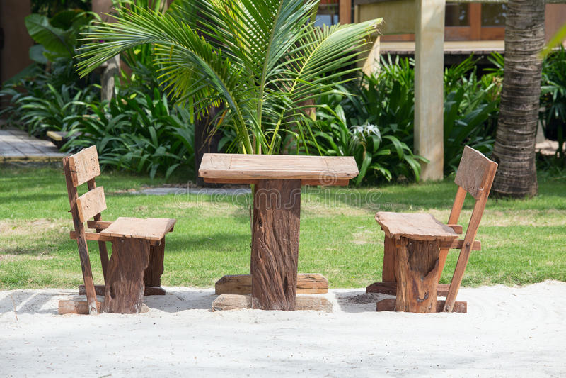 Esvazie a tabela e cadeiras de madeira de um jardim tropical da praia perto do mar imagens de stock royalty free