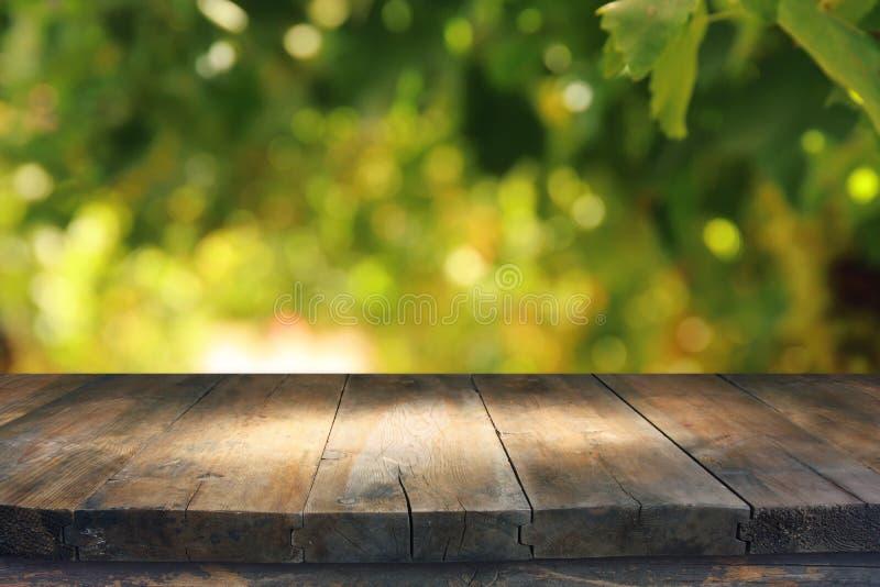 Esvazie a tabela rústica na frente do fundo verde do bokeh do sumário da mola exposição do produto e conceito do piquenique foto de stock