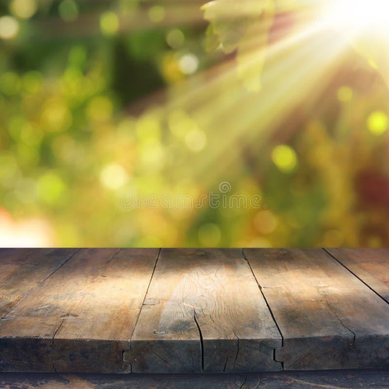 Esvazie a tabela rústica na frente do fundo verde do bokeh do sumário da mola exposição do produto e conceito do piquenique fotografia de stock royalty free