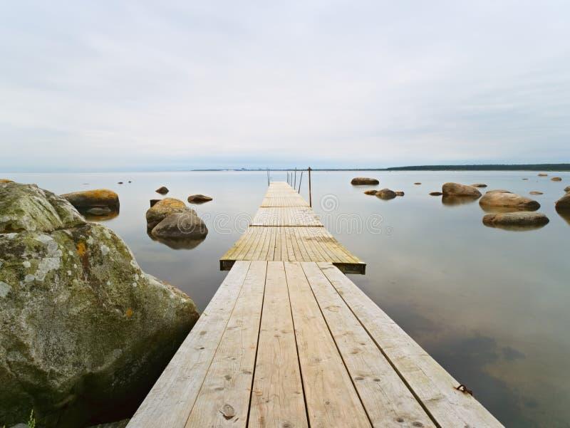 Esvazie a toupeira de madeira na água do lago azul Cais velho da pesca para barcos e nadadores contratados fotografia de stock royalty free