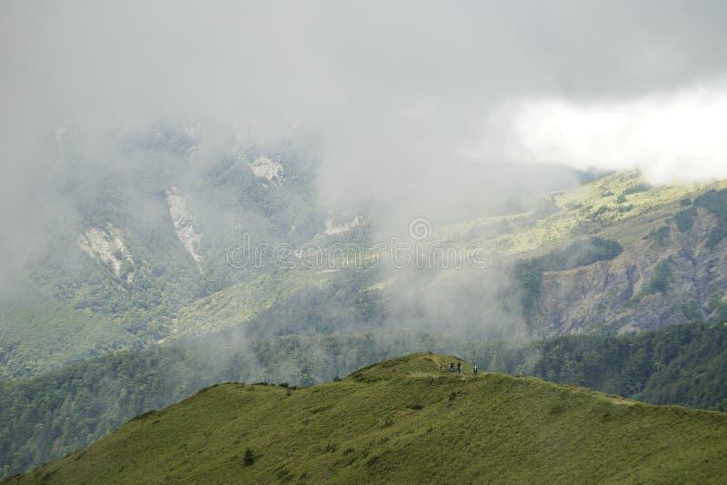 Esverdeie altamente a montanha e o céu azul nebuloso, uso apropriado como um fundo imagens de stock