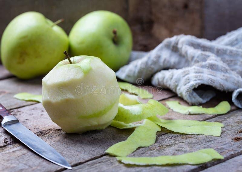 Esverdeie a maçã descascada na mesa de madeira com faca e maçãs atrás fotos de stock