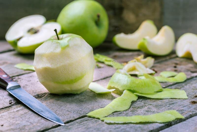 Esverdeie a maçã descascada no fundo de madeira rústico natural imagens de stock royalty free