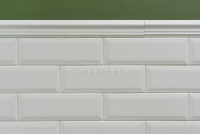 Esverdeie a parede pintada, peça da parede é tijolo lustroso branco pequeno coberto das telhas, telhas decorativas cerâmicas do m imagem de stock