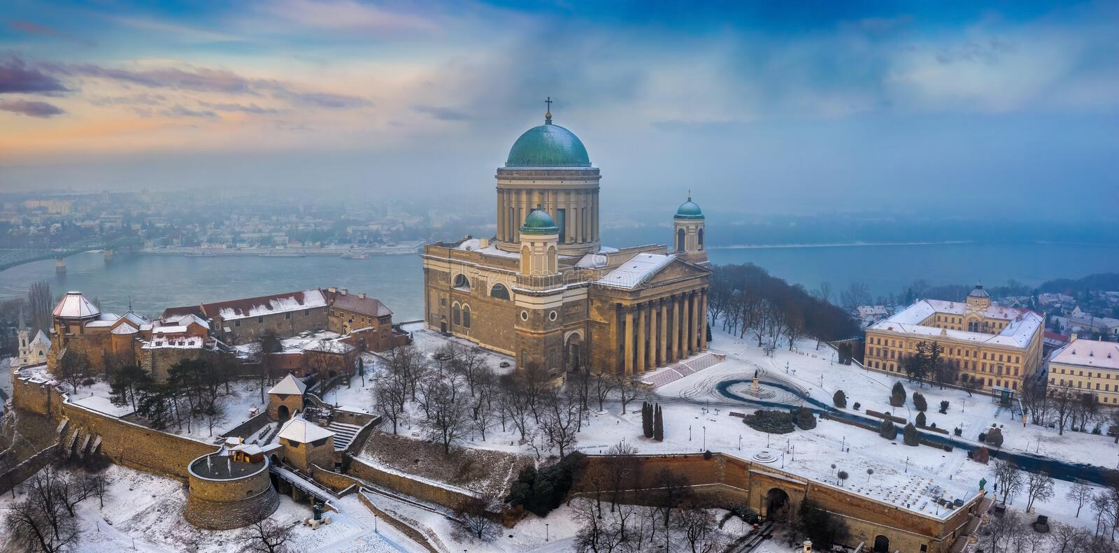 Esztergom, Hungary - Aerial panoramic view of the beautiful snowy Basilica of Esztergom with Slovakia at the background. On a foggy winter morning royalty free stock photography