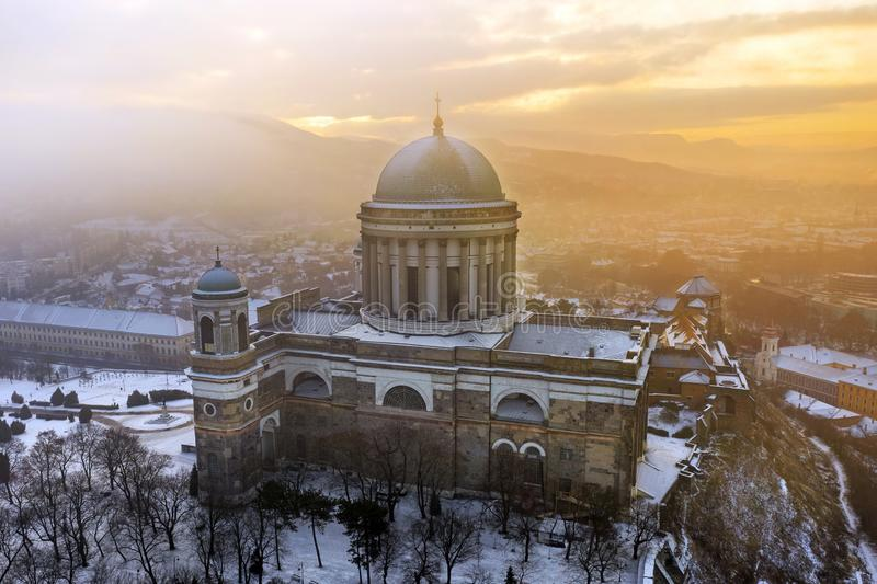 Esztergom, Hungary - Aerial view of the beautiful snowy Basilica of Esztergom on a foggy winter morning. With golden sunrise stock photo