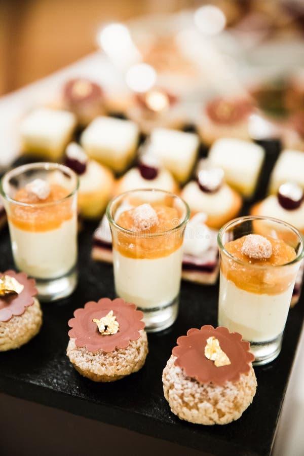 Or et argent déjoués épousant des desserts et des mousses photos stock