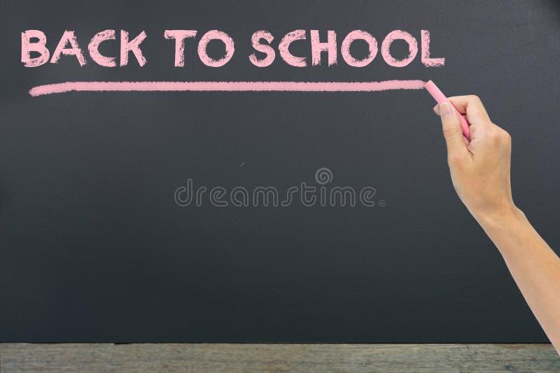 et x22 ; De nouveau au school& x22 ; écrit par la craie rose sur la craie noire d'école photographie stock