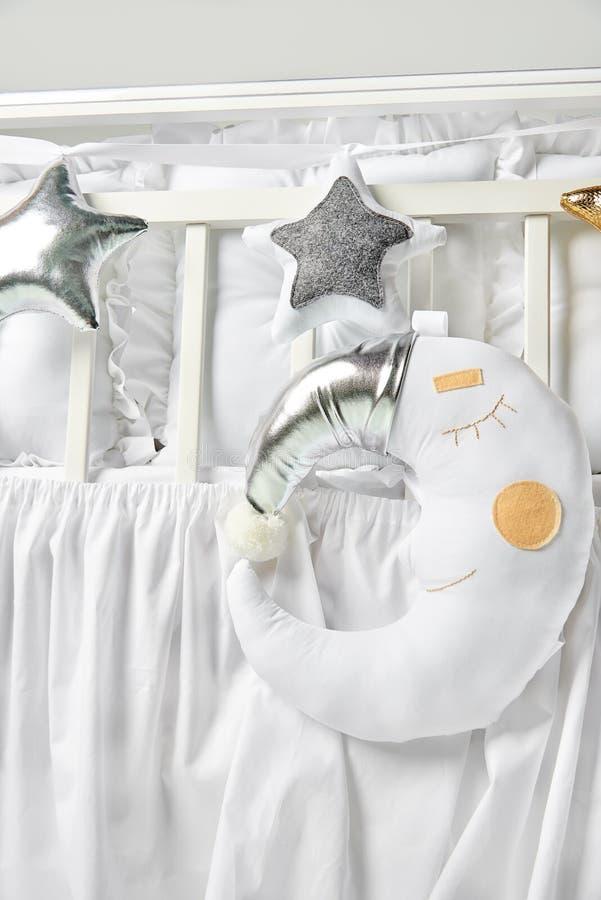 Or et oreillers et coussin en forme d'étoile blancs de lune de sommeil sur un berceau de bébé blanc photographie stock libre de droits