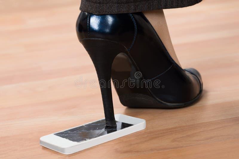 Etapa do salto alto em smartphone quebrado fotografia de stock