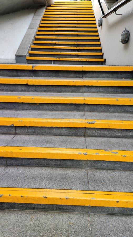 Etapas amarelas perto do estação de caminhos de ferro local fotografia de stock