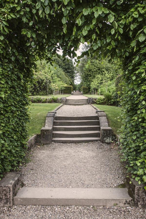 Etapas através do arco aos jardins ajardinados formais imagem de stock royalty free