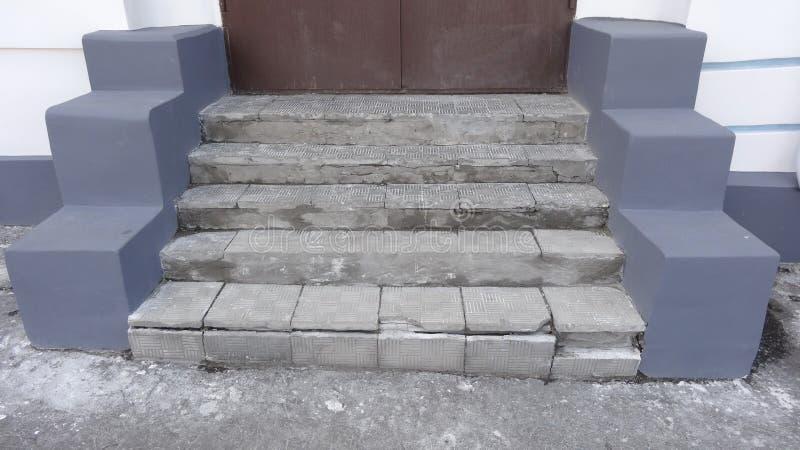 Etapas cinzentas de pedra velhas com sinais do desgaste da destruição com riscos e quebras à porta vermelha na rua imagem de stock