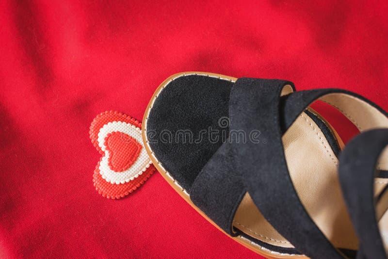 Etapas da sapata de uma mulher negra no coração em um fundo vermelho Configura??o lisa foto de stock