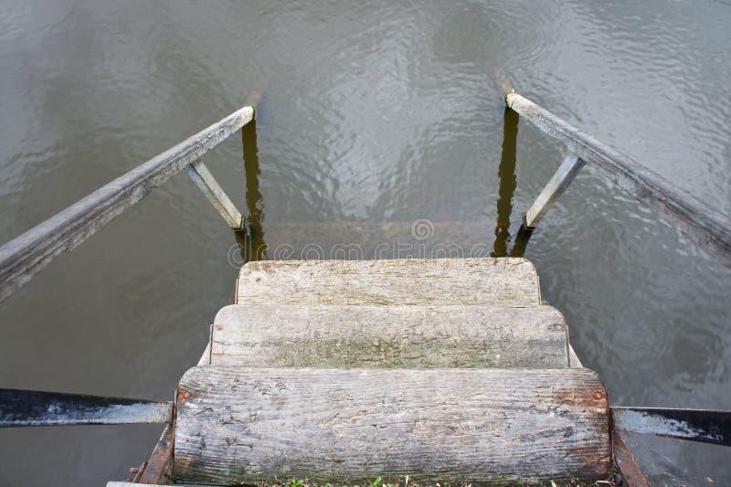 Etapas de madeira com os corrimão que conduzem à água com uma reflexão do céu foto de stock
