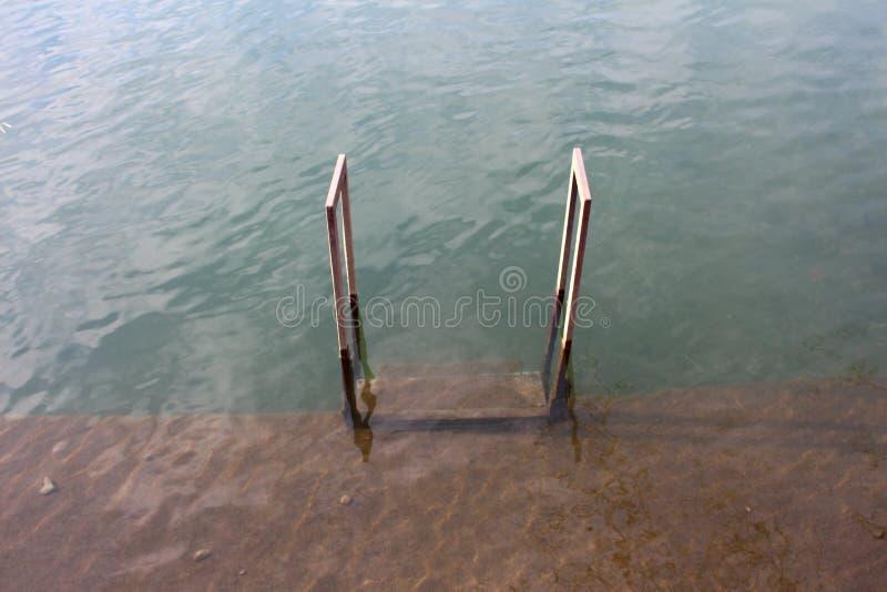 Etapas inundadas do metal cobertas com a lama que conduz ao rio de transbordamento foto de stock