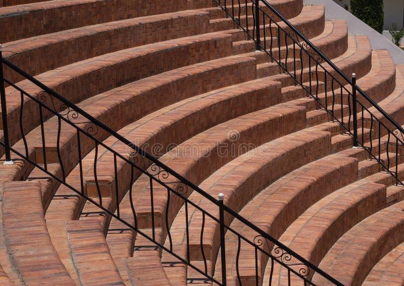 Etapas semicirculares no setor com os trilhos pretos do metal, um fragmento do anfiteatro dos assentos - etapas fotografia de stock