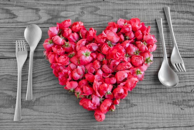 Etend in liefde, een hart met rode rozenbloesems die wordt gemaakt stock foto's