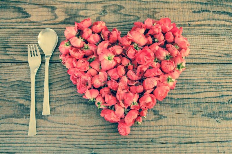 Etend in liefde, een hart met rode rozenbloesems die wordt gemaakt stock fotografie