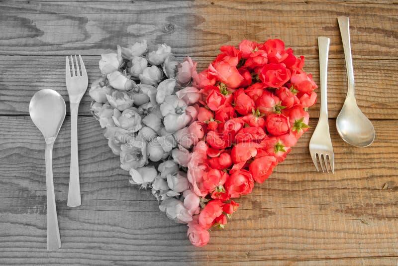 Etend in liefde, een hart met rode rozenbloesems die wordt gemaakt stock afbeeldingen
