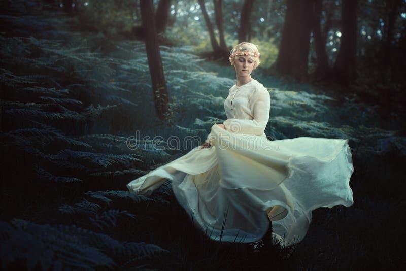 Eterisk kvinnadans i drömlik skog fotografering för bildbyråer